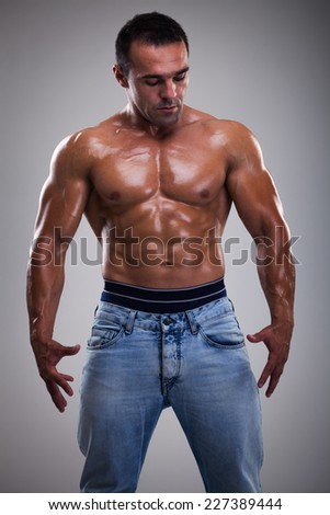 Portrait of a handsome muscular bodybuilder posing over gray background.