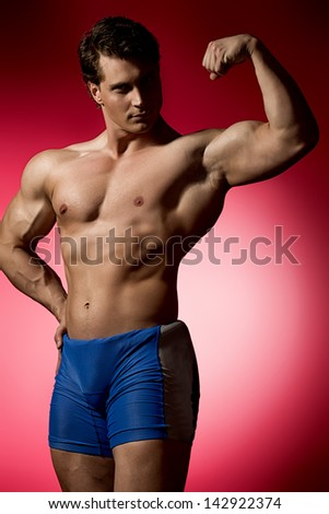 Portrait of a handsome muscular bodybuilder posing over red background. - stock photo