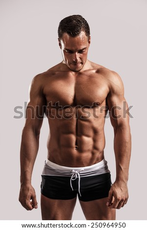 Portrait of a handsome muscular man in black beach shorts isolated on white in studio.
