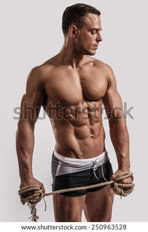 Portrait of a handsome muscular man in black beach shorts with rope in his hand isolated on white in studio.