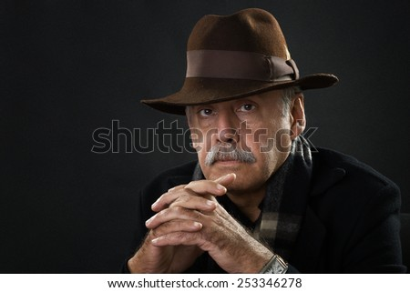 portrait of a handsome old man wearing a cowboy hat - stock photo
