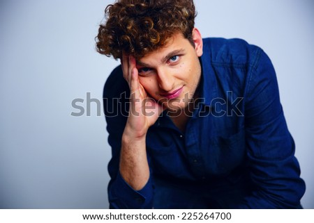 Portrait of a handsome pensive man with curly hair - stock photo