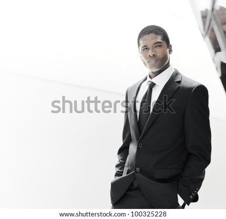 Portrait of a handsome powerful young executive against bright modern background with copy space - stock photo