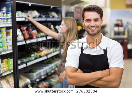 Portrait of a handsome seller with arm crossed at supermarket - stock photo