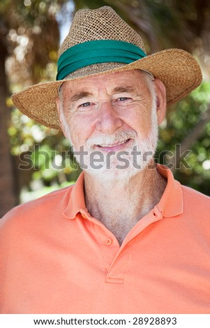 Portrait of a handsome senior man in a straw hat. - stock photo