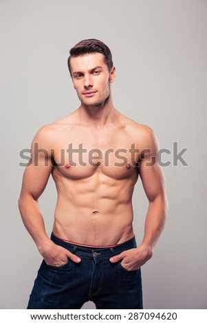 Portrait of a handsome sexy man posing over gray background and looking at camera - stock photo