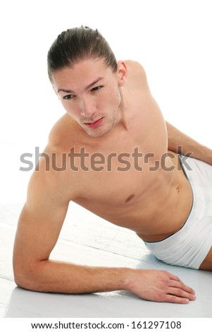 Portrait of a handsome shirtless man who is working out and posing over a white background