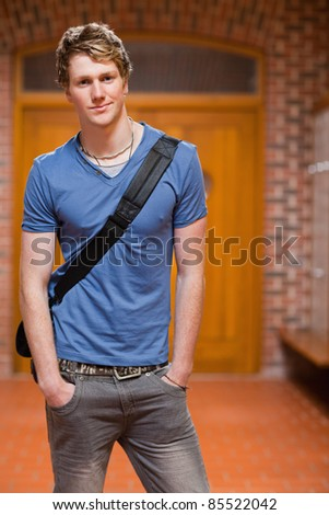 Portrait of a handsome student standing up in a corridor - stock photo