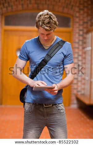 Portrait of a handsome student using a tablet computer in a corridor - stock photo