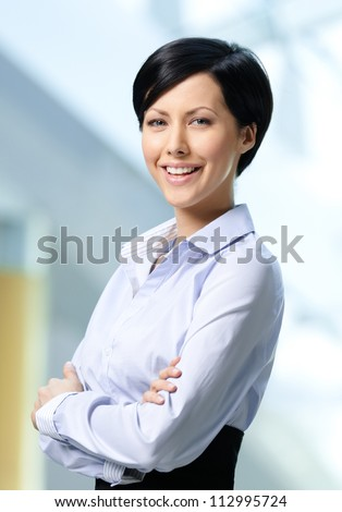 Portrait of a handsome successful business woman wearing white shirt and black skirt at business centre - stock photo