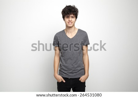 Portrait of a Handsome Teenager Standing and Posing in the Studio - stock photo