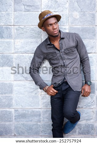 Portrait of a handsome young african american man leaning against wall - stock photo