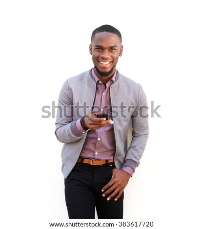 Portrait of a handsome young african man standing with a mobile phone against white background - stock photo