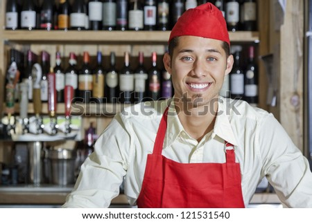 Portrait of a handsome young bartender smiling in bar