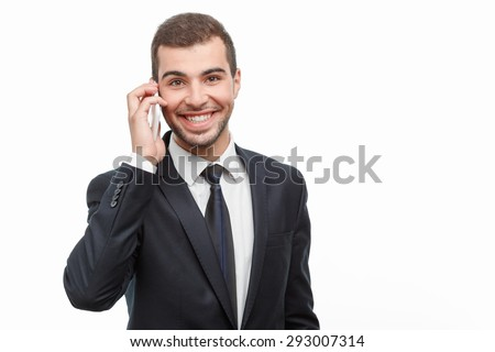 Portrait of a handsome young bearded man wearing a formal black suit and talking on his mobile phone and smiling, isolated on white background - stock photo