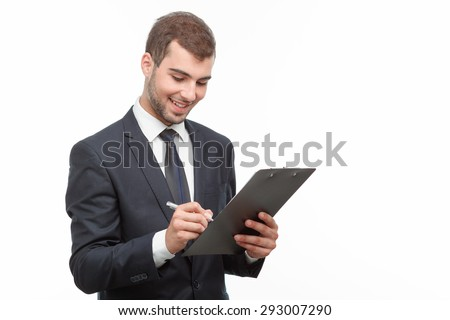 Portrait of a handsome young bearded man wearing a formal black suit holding a paper holder and writing something smiling, isolated on white background - stock photo