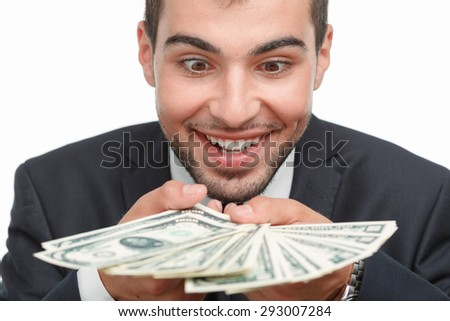 Portrait of a handsome young bearded man wearing a formal black suit holding many dollar bills in front of his face looking very happy, isolated on white background - stock photo