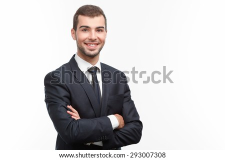 Portrait of a handsome young bearded man wearing a formal black suit standing crossing his arms smiling, isolated on white background - stock photo