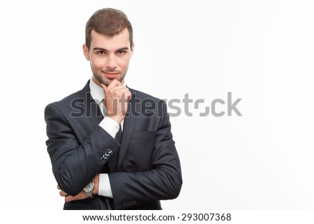 Portrait of a handsome young bearded man wearing a formal black suit standing smiling and holding his hand on his chin looking foxy, isolated on white background - stock photo