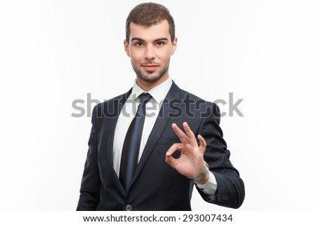 Portrait of a handsome young bearded man wearing a formal black suit standing smiling and showing ok sigh, isolated on white background - stock photo