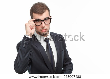 Portrait of a handsome young bearded man wearing a formal black suit touching his glasses and looking seriously at the camera, isolated on white background - stock photo