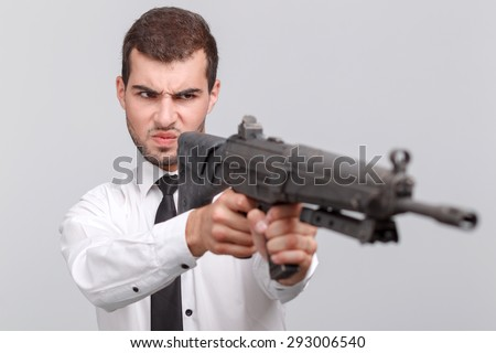 Portrait of a handsome young bearded man wearing white shirt and a tie holding rifle gun and shooting angrily, isolated on grey background - stock photo
