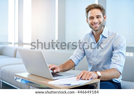 Portrait of a handsome young business entrepreneur, sitting in a modern business lounge and smiling at the camera with his laptop open in front of him - stock photo