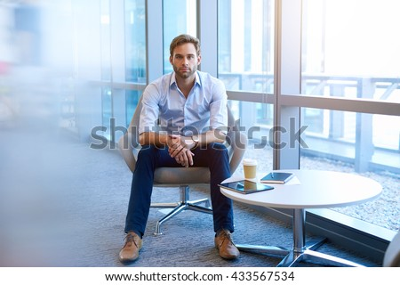 Portrait of a handsome young business executive sitting in a bright corporate space in a modern chair, facing the camera with legs open and hands folded, and a straight-forward serious expression - stock photo