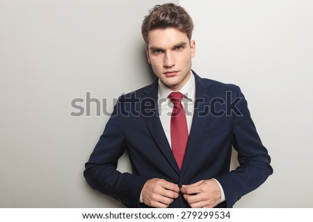 Portrait of a handsome young business man closing his jacket while looking at the camera.