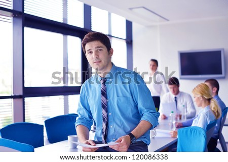 Portrait of a handsome young  business man  on a meeting in offce with colleagues in background - stock photo