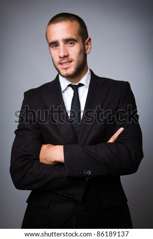 Portrait of a handsome young business man on grey background - stock photo