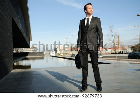 Portrait of a handsome young business man standing in the street