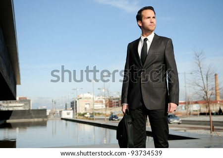 Portrait of a handsome young business man standing in the street - stock photo
