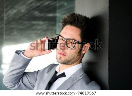Portrait of a handsome young business man talking on mobile phone