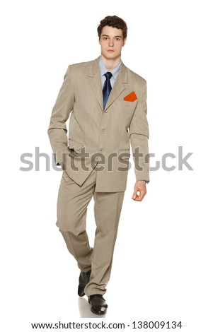 Portrait of a handsome young business man walking on white background with blank credit card in his breast pocket - stock photo