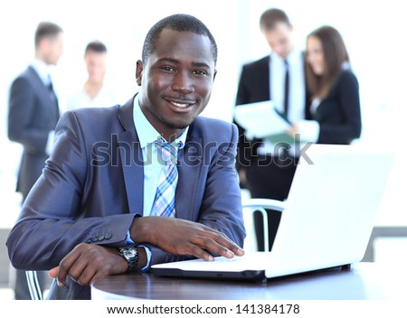 Portrait of a handsome young business man with a laptop - stock photo