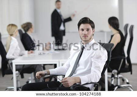 Portrait of a handsome young business man with people  in background at office meeting - stock photo