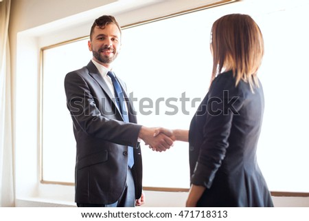 Portrait of a handsome young businessman giving a handshake to a female client and making eye contact