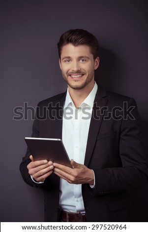 Portrait of a Handsome Young Businessman Holding his Tablet Computer, Smiling at the Camera Against Gray Wall Background. - stock photo