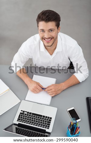 Portrait of a Handsome Young Businessman Sitting at his Desk with Laptop and Notes, Smiling at the Camera from High Angle View. - stock photo