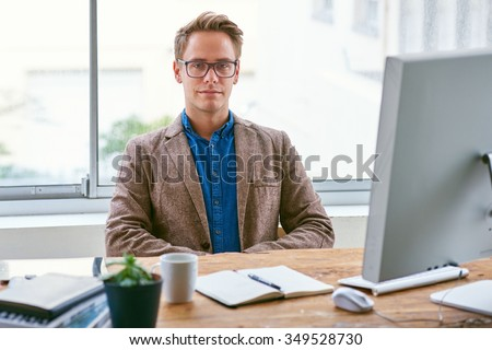 Portrait of a handsome young businessman sitting confidently behind his desk looking straight at the camera in a bright contemporary office space - stock photo