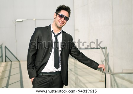 Portrait of a handsome young businessman smiling with sunglasses - stock photo