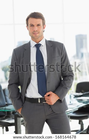 Portrait of a handsome young businessman standing in a bright office - stock photo