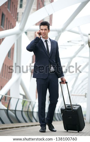Portrait of a handsome young businessman traveling with bag and talking on phone at station - stock photo