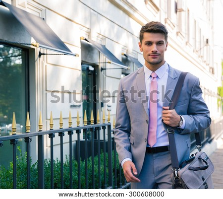 Portrait of a handsome young businessman walking in the city - stock photo