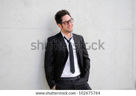 Portrait of a handsome young businessman with eyeglasses smiling - stock photo