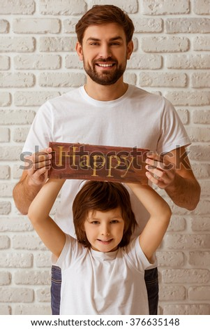 "Portrait of a handsome young father and his cute little son holding a wooden plate ""happy"", looking in camera and smiling. Both in white t-shirts and jeans, standing against white brick wall. - stock photo"