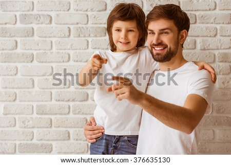 Portrait of a handsome young father holding his cute little son. Both in white t-shirts and jeans pointing and smiling, standing against white brick wall. - stock photo