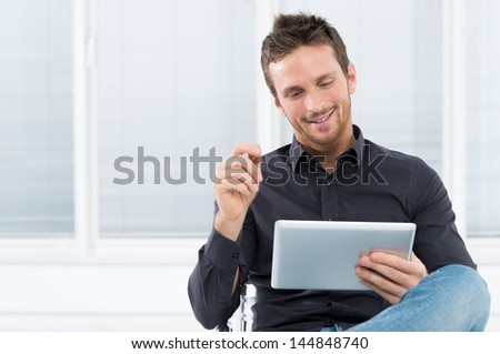 Portrait Of A Handsome Young Happy Man Using Digital Tablet - stock photo