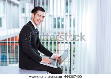 Portrait Of A Handsome Young Happy Man Using laptop in office - stock photo